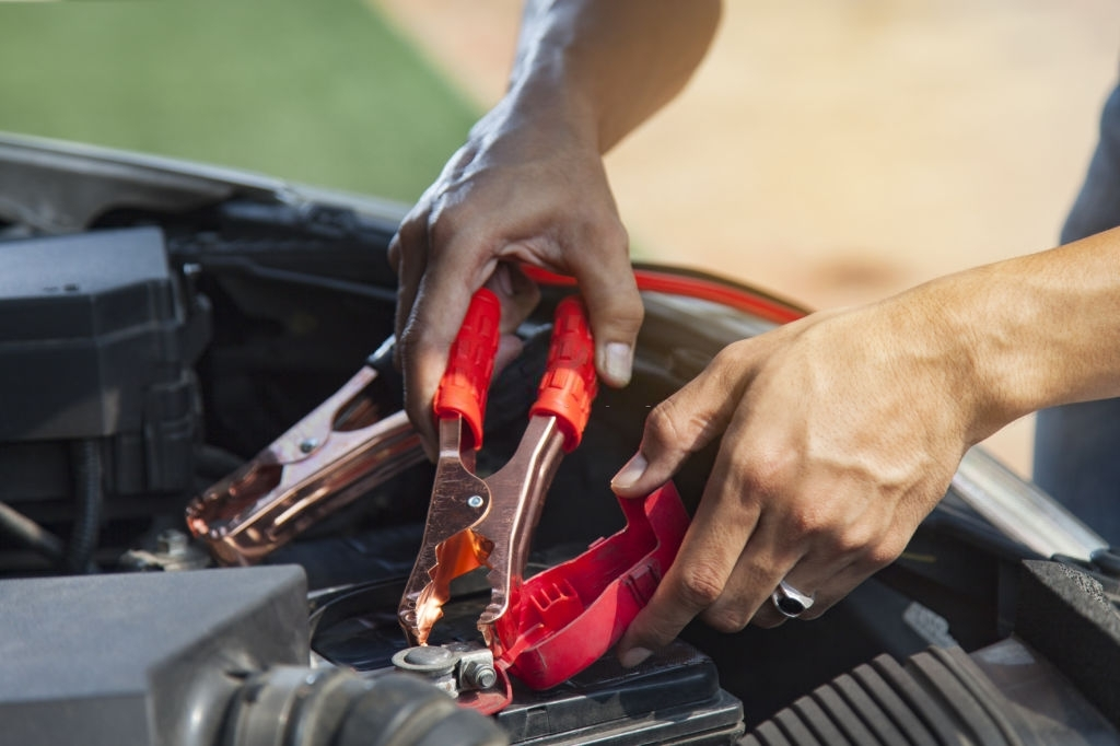 Man using battery jumper cables on a dead battery