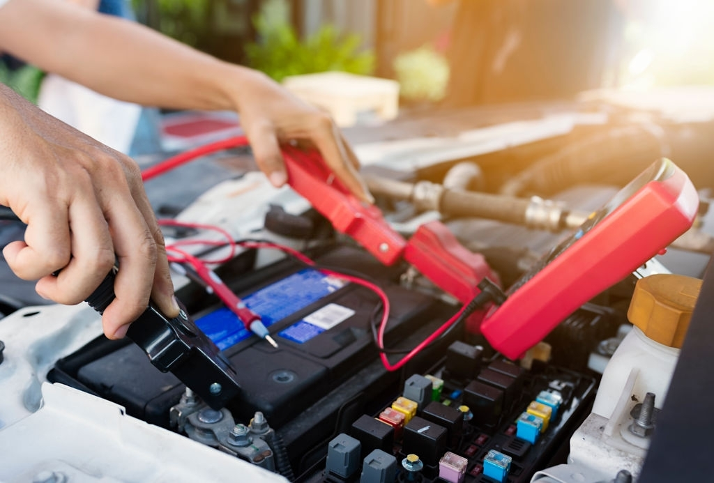Close up of auto mechanic jumping battery car.