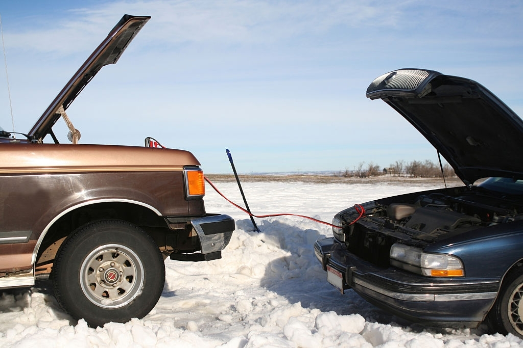 Two vehicles, one jumpstarting the other after a blizzard.