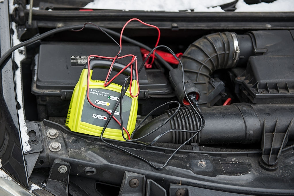 charging a car battery with red and black cable connected